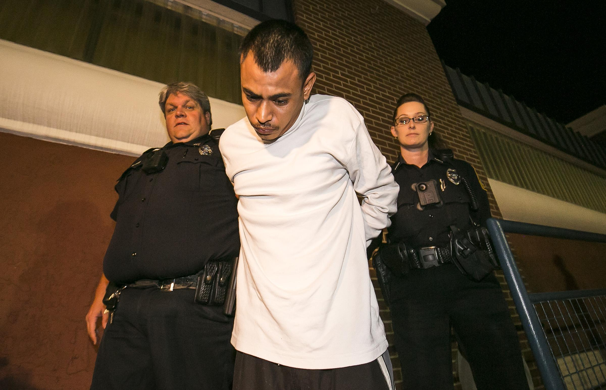 Ocala police officers William Joedicke, left, and Rebecca Letson walk Joshua Zuniga, 29, out of the Ocala Police Department. (Photo credit: Doug Engle/Ocala Star-Banner.)